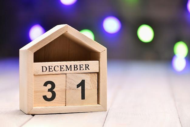Houten blokjes met de cijfers 31 december en wazige slinger