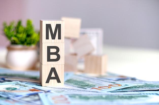 Houten blokjes met de letters mba gerangschikt in een verticale piramide op bankbiljetten, groene plant in een bloempot op de achtergrond.