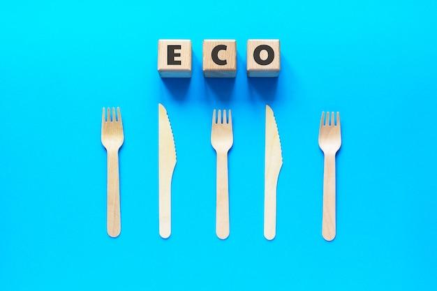 Houten blokjes met tekst eco, houten vorken en messen op blauw