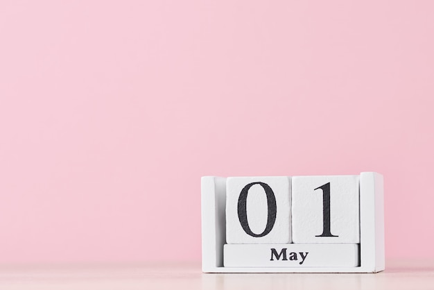 Houten blokkalender met datum 1 mei op roze. dag van de arbeid concept