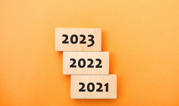Houten blokken 2021 2022 2023 het concept van het begin van het nieuwe jaar nieuwe doelen volgend decennium