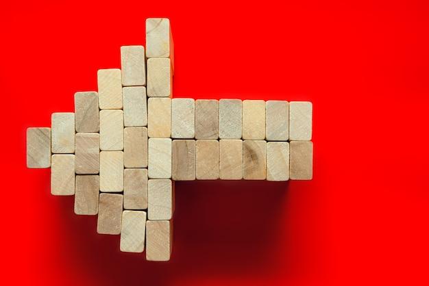 Houten blokken. een pijlsymbool dat bij het rood wordt geïsoleerd