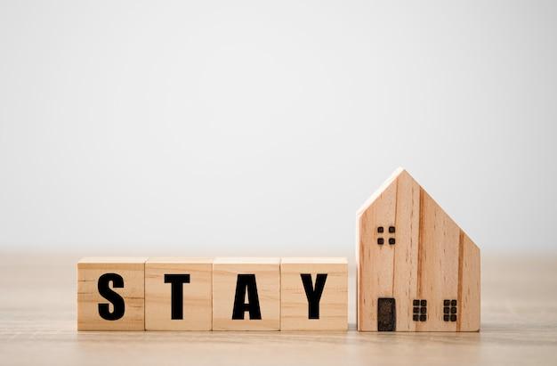 Houten blokken kubus formulering verblijf met houten huis. blijf thuis om te voorkomen dat covid 19 uitbreekt.