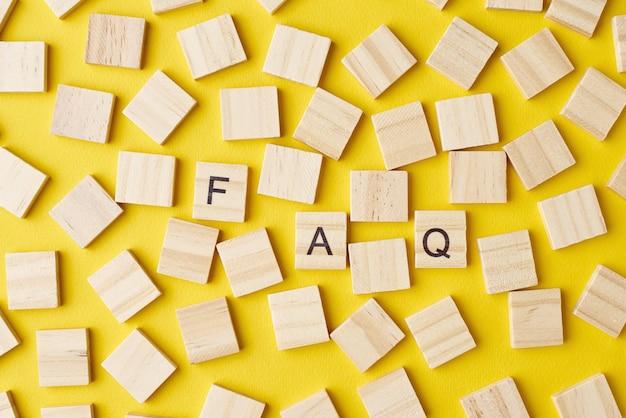 Houten blokken met afkorting faq op gele achtergrond, bovenaanzicht. veelgestelde vragenconcept