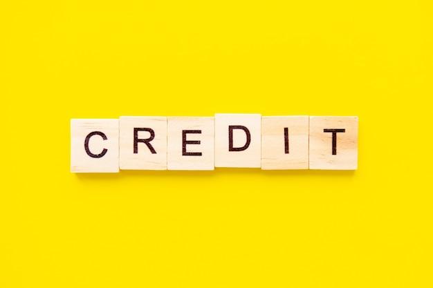 Houten blokken met de belettering woord krediet bovenop gele tafel. zakelijke en financiële concept.
