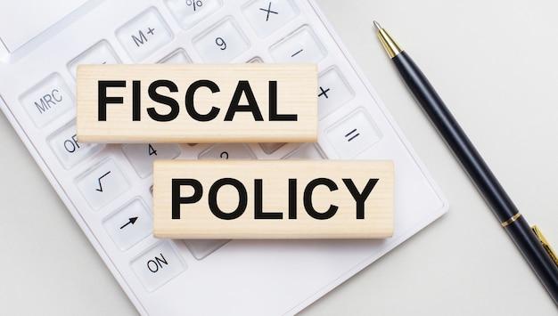 Houten blokken met de tekst fiscal policy liggen op een lichte achtergrond op een witte rekenmachine. vlakbij is een zwart handvat. bedrijfsconcept