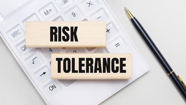 Houten blokken met de tekst risk tolerantie liggen op een lichte achtergrond op een witte rekenmachine. vlakbij is een zwart handvat. bedrijfsconcept