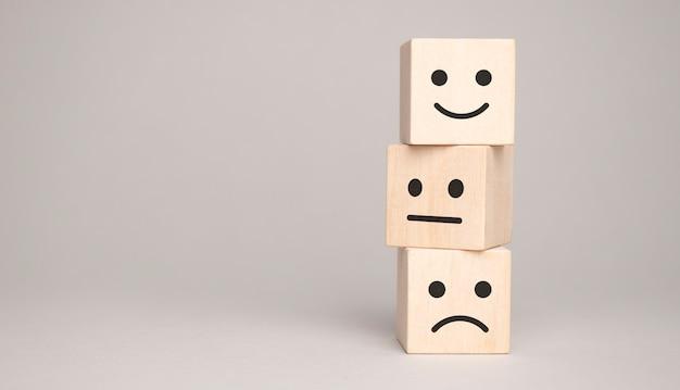 Houten blokken met het blije gezicht glimlach symbool symbool op de tafel, evaluatie,