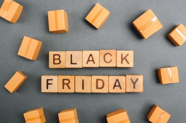 Houten blokken met het woord black friday en de dozen. grote verkoop en kortingen. lage prijzen.