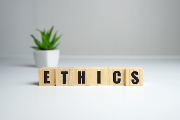 Houten blokken met het woord ethiek. begrippen van goed en fout gedrag verdedigen, systematiseren en aanbevelen. morele filosofie
