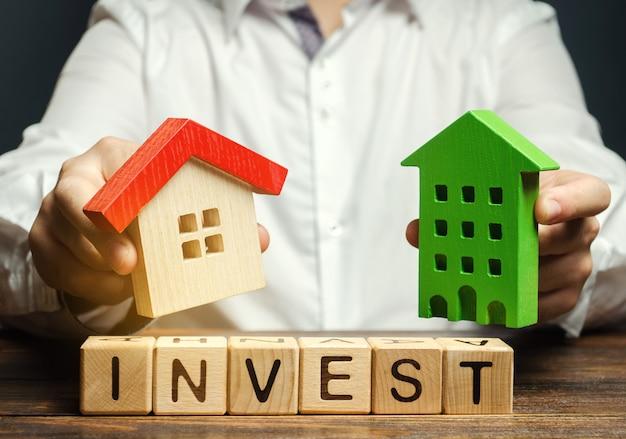 Houten blokken met het woord invest en huizen