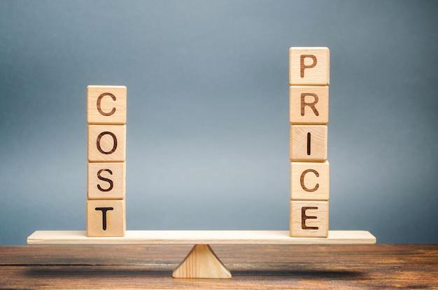 Houten blokken met het woord kosten en prijs op de weegschaal. het concept van gelijkwaardigheid.