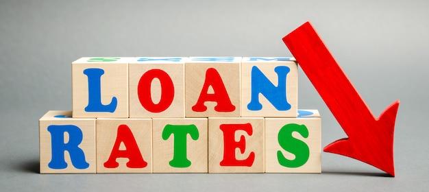 Houten blokken met het woord leningstarieven en pijl naar beneden. de lage hypotheekrente.