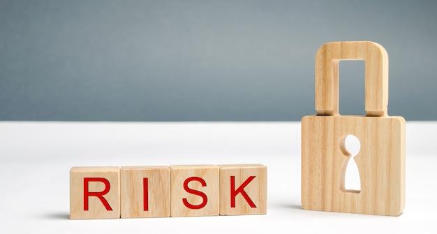 Houten blokken met het woord risico en slot. imperfect beveiligingssysteem. hoog risico om te hacken