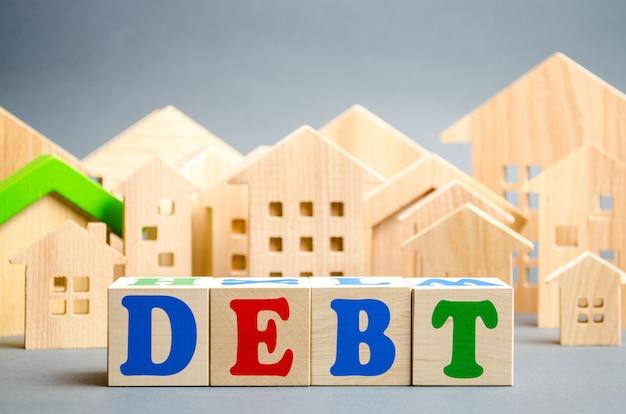 Houten blokken met het woord schulden en miniatuur huizen.