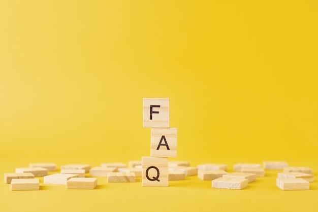 Houten blokken met woord faq op gele achtergrond