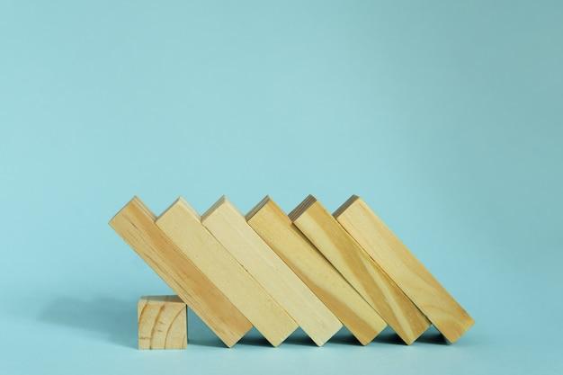 Houten blokken op blauwe achtergrond. domino-effect in bedrijfsconcept.