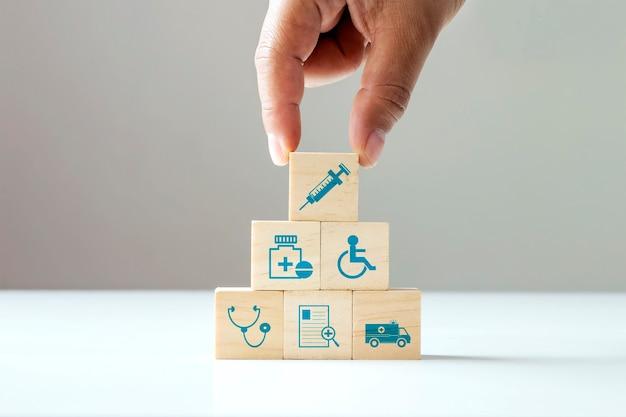Houten blokken stapelen menselijke hand gezondheidszorg pictogrammen en medische pictogrammen