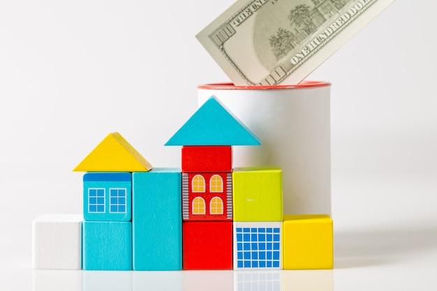 Houten blokken vormige huizen en spaarpot