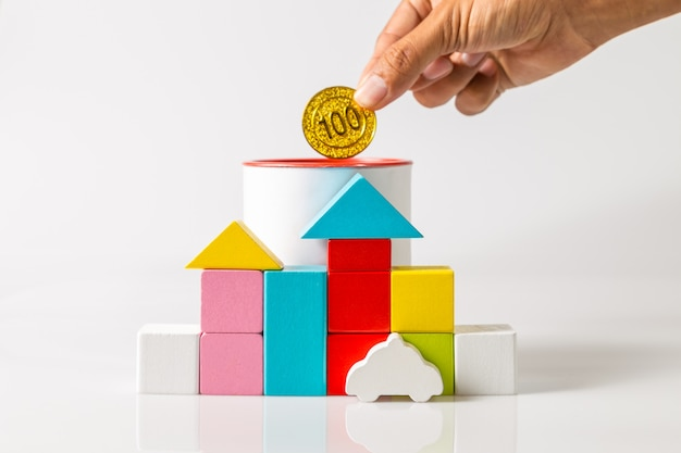 Houten blokken vormige huizen, modelauto en spaarpot