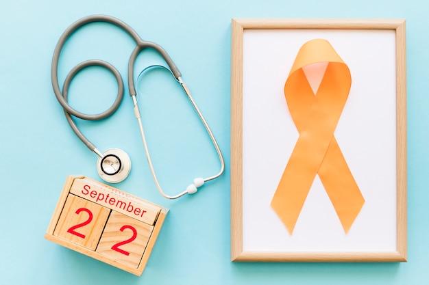 Houten blokkenkalender 22 september, stethoscoop en oranje lint voor meervoudig bewustzijn