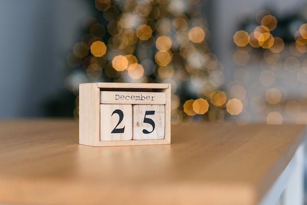 Houten blokkenkalender met de datum van 25 december op de kerstverlichting. wintervakantie stemming.