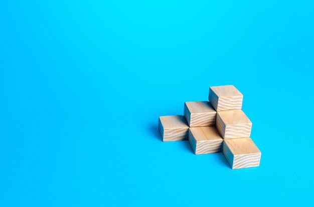Houten blokkenpiramide op een blauwe achtergrond. minimalisme. eenvoudige vormengeometrie