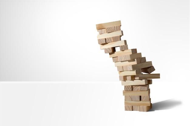 Houten blokkentoren spel instortingen geïsoleerd op wit