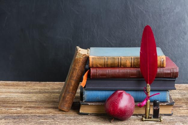 Houten boekenrek met antieke boeken, appel en rode verenpen
