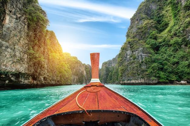 Houten boot die met lange staart op het kalksteenberg van de lagune pileh in krabi, thailand vaart