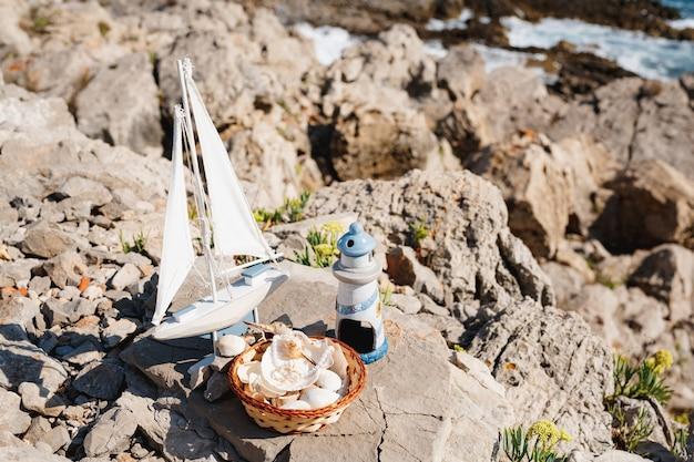 Houten boot en blauwe vuurtoren en schelpen op het rotsachtige strand