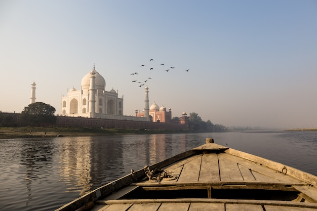 Houten boot op de yamuna-rivier met taj mahal en vogelvlieg over.