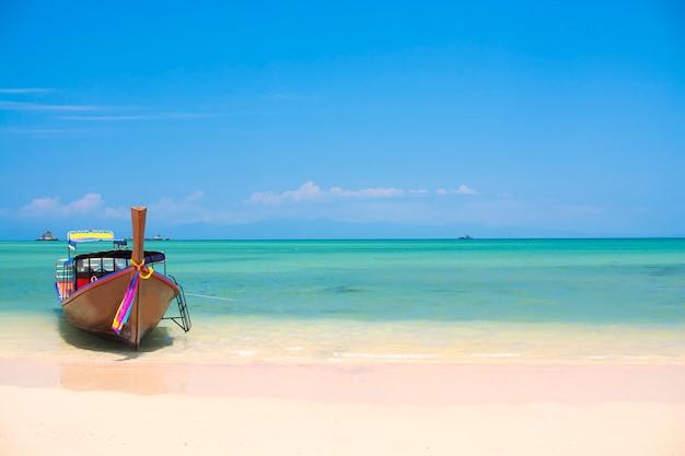 Houten boot op een wit zandstrand, tropisch strand in thailand