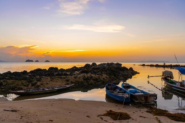 Houten boot voor de kust van een tropisch eiland. avond, zonsondergang in de oceaan. tropisch landschap. lichtgolven wiegen de boot