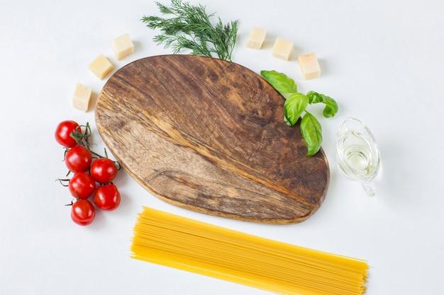 Houten bord, eromheen zijn tomaten, olijfolie, dille, kaas, basilicum en spaghetti pasta