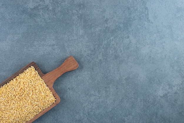 Houten bord gevuld met tarwekorrel op marmer
