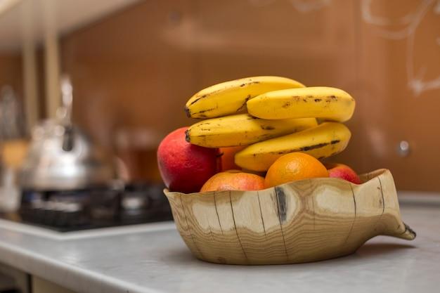 Houten bord kom met verse heerlijke lekkere fruit appels. bananen en oranje op wit keukentafel op lichte onscherpe achtergrond.