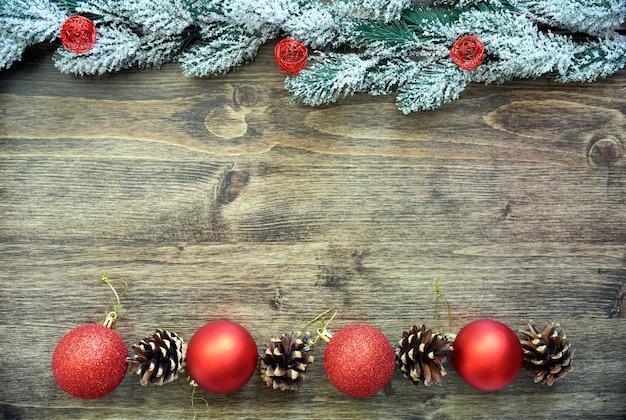 Houten bord met besneeuwde dennentakken, kerstboomspeelgoed en dennenappels