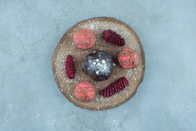 Houten bord met een cake, koekjes en dennenappels op marmer.