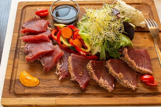 Houten bord met een tonijn tataki en gekiemde groenten op een tafel
