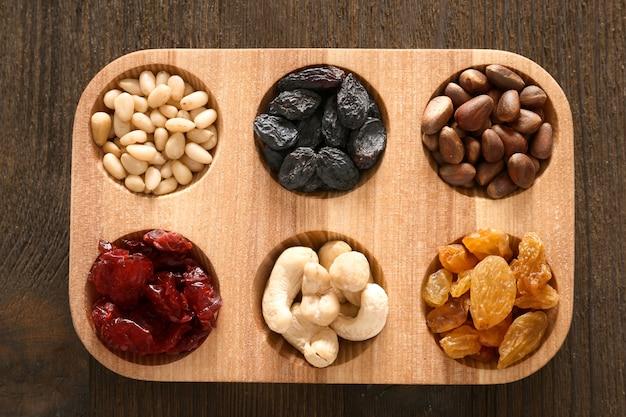 Houten bord met gedroogde vruchten en noten op tafel, bovenaanzicht