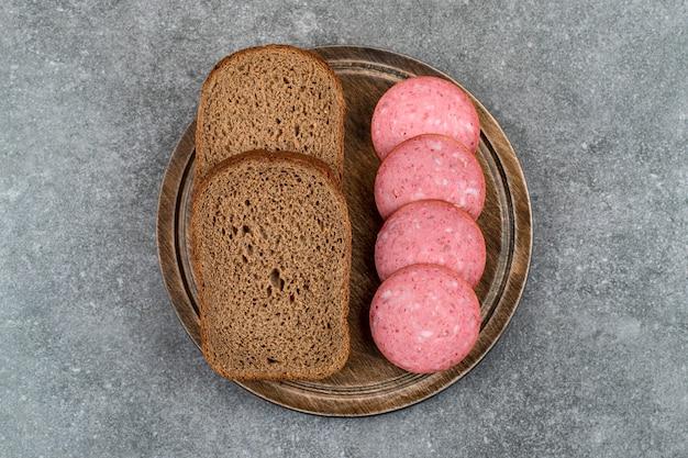 Houten bord met gesneden salami op stenen tafel.