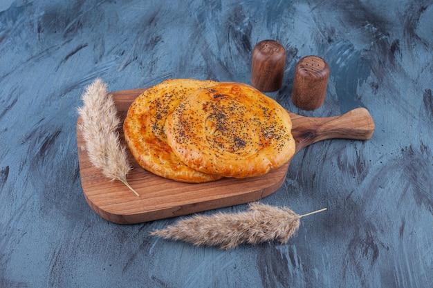 Houten bord met heerlijke geurige gebakjes op marmer.