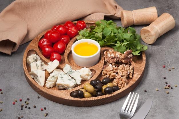 Houten bord met kaas, noten, tomaten en olijven
