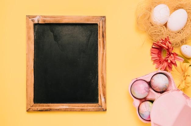 Houten bord met paaseieren en gerberabloemen op gele achtergrond