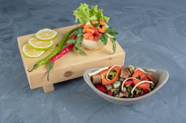 Houten bord met plakjes citroen en een portie groenten naast een kom groentesalade op marmeren oppervlak.
