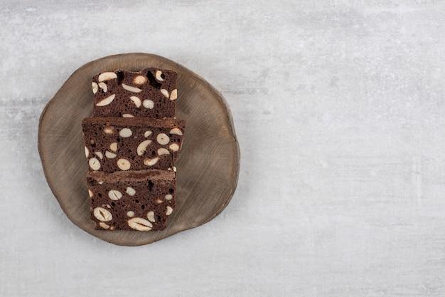Houten bord met sneetjes bruin brood met noten op een stenen tafel.