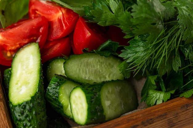 Houten bord met veel kruiden en groenten. tomaten komkommers. peterselie en dille. detailopname. vegetarisme, vitamines en gezondheid uit de natuur.