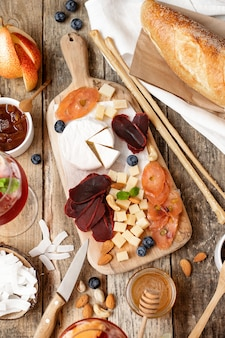 Houten bord met verschillende soorten kaas, vlees, fruit, noten, stokbrood op een houten tafel. rustieke stijl. franse proeverij.