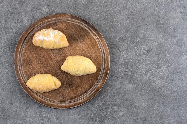 Houten bord met zelfgemaakte verse koekjes op marmeren tafel.